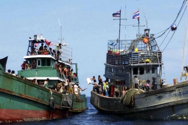 Un bateau de pêcheurs thaïlandais donne des vivres... (PHOTO REUTERS)