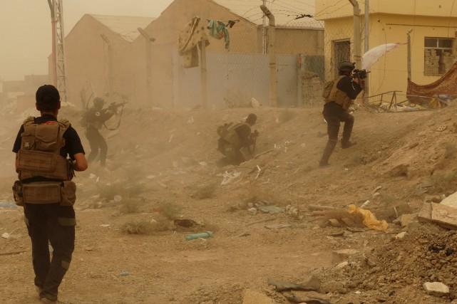 Des membres des forces de sécurité irakiennes défendent... (PHOTO REUTERS/STRINGER)