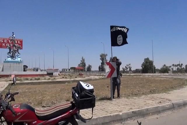 Un homme accroche un drapeau de l'État islamiste... (Photo tirée de YouTube)