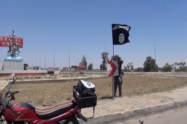 Un combattant de l'EI installe un drapeau de... (IMAGE AFP)