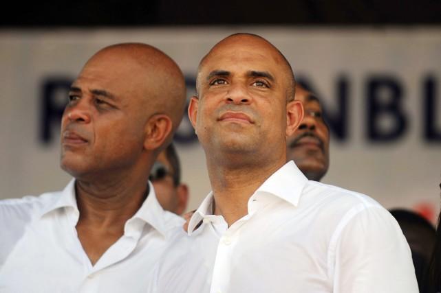 Laurent Lamothe (à droite), alors premier ministre, en... (PHOTO HECTOR RETAMAL, ARCHIVES AFP)