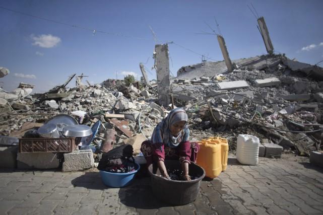 Une femme lave le linge devant sa maison,... (Photo Khalil Hamra, archives AP)