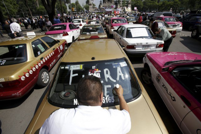 Un chauffeur de taxi inscrit le slogan «Dehors... (PHOTO ADAN GUTIERREZ, REUTERS)