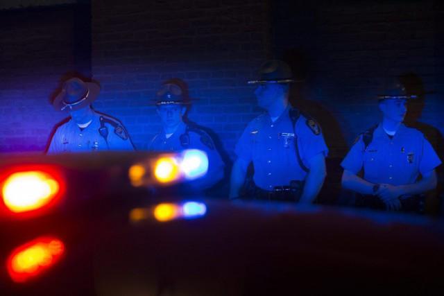 Des policiers sont illuminés par des gyrophares lors... (PHOTO JOHN MINCHILLO, AP)