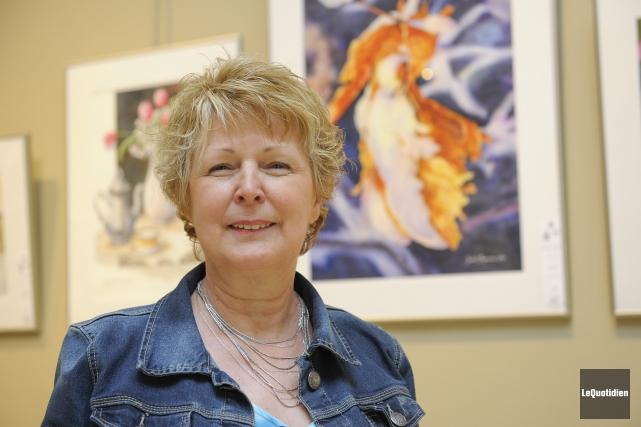 Photographiée devant son tableau, Étincelle, Judith Tremblay affirme... (Photo Le Quotidien, Gimmy Desbiens)