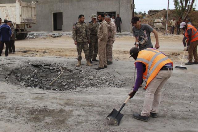 Des travailleurs nettoient le site d'un attentat suicide... (PHOTO REUTERS)
