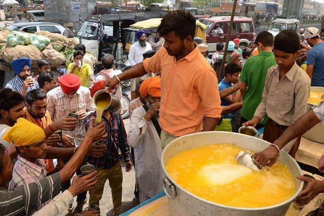 Des bénévoles distribuent du jus à des passants... (PHOTO NARINDER NANU, AFP)