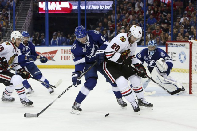 Brandon Saad (20) et Anton Stralman (6) se disputent... (PHOTO KIM KLEMENT, USA TODAY SPORTS)