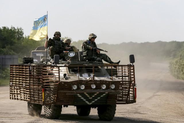 Des membres de forces ukrainiennes patrouillent près de... (PHOTO GLEB GARANICH, REUTERS)