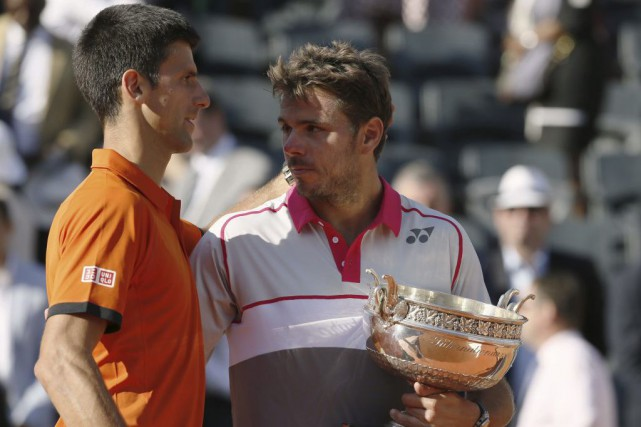 Novak Djokovic reçoit l'accolade du champion des Internationaux... (Patrick Kovarik, AFP)