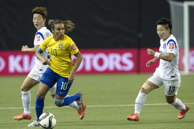 La joueuse brésilienne Marta entourée de deux Sud-Coréennes... (Photo: AFP)