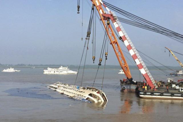 Des grues tirent le navire «L'Étoile de l'Orient»... (PHOTO CHINA OUT / ARCHIVES AFP)