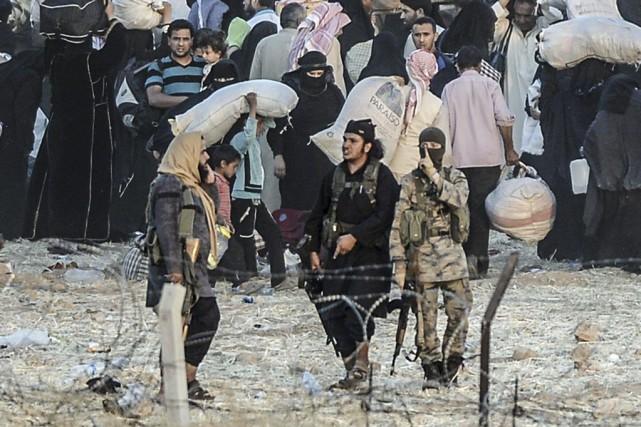 Des djihadistes de l'État islamiquerepoussent des réfugiés à... (PHOTO BULENT KILIC, AFP)