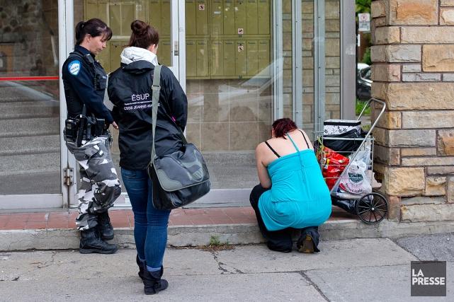 Des policiers discutent avec une femme sous l'emprise... (PHOTO DAVID BOILY, LA PRESSE)