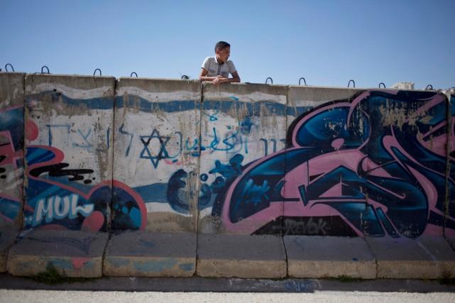 Un jeune Palestinien est appuyé sur un mur... (PHOTO ARIEL SCHALIT, ARCHIVES AP)