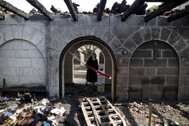 Les flammes ont emporté la toiture, laissant apparaître... (PHOTO ARIEL SCHALIT, AP)