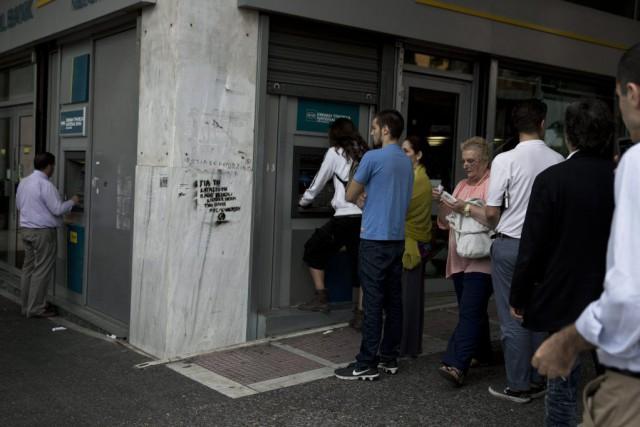 Les Grecs étaient nombreux vendredi à aller retirer... (Photo Petros Giannakouris, AP)