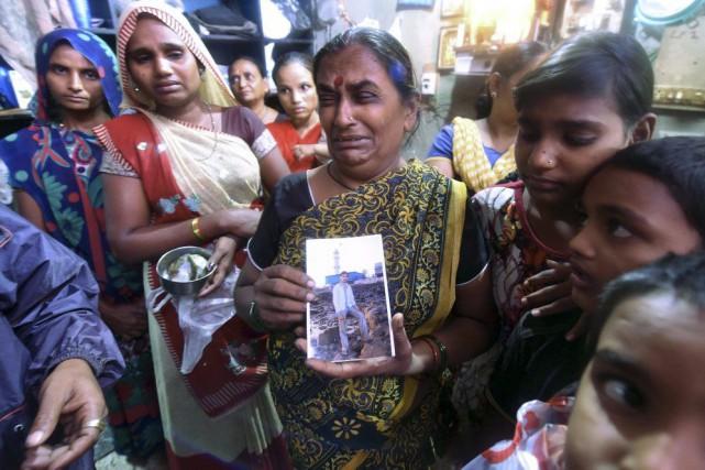 Une femme tient la photo d'un homme décédé... (PHOTO AFP)