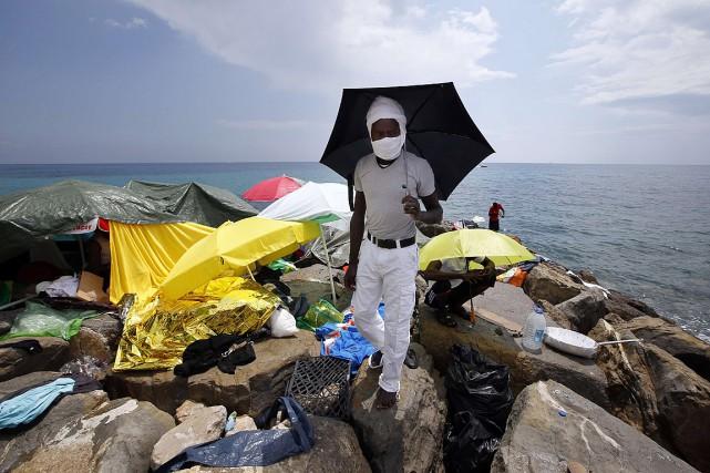 Un migrant se protège du soleil sous un... (PHOTO VALERY HACHE, AFP)