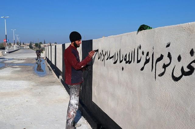 Un membre de l'EI peinture sur un mur... (ARCHIVES AFP)