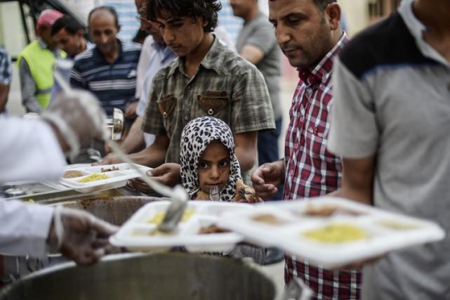 Des réfugiés syriens rompent leur jeûne du ramadan... (PHOTO AFP)