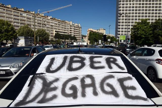 Un taxi avec une bannière invitant Uber à... (PHOTO ANNE-CHRISTINE POUJOULAT, AFP)