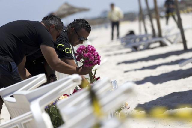 Des tunisiens déposent des gerbes de fleurs sur... (PHOTO KENZO TRIBOUILLARD, AFP)