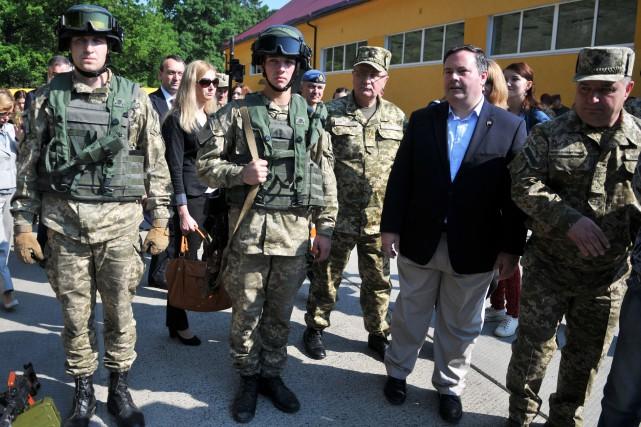 Le ministre Jason Kenney (veston noir) lors de... (Photo Pavlo Palamarchuk, AP)