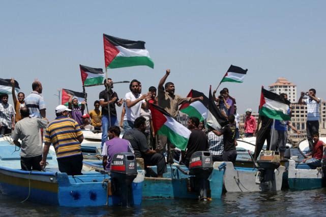 Des Palestiniens de Gaza brandissent leur drapeau en... (PHOTO AFP)