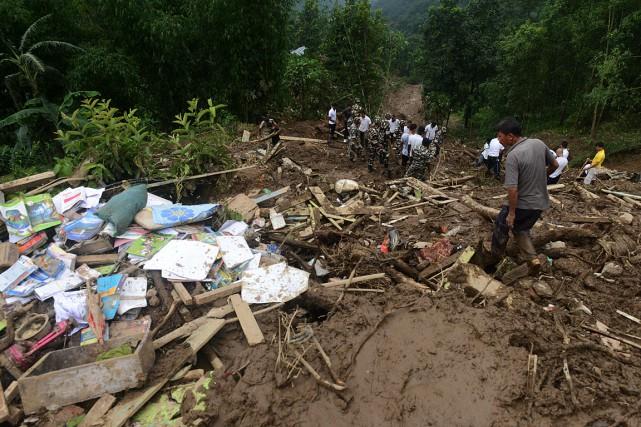 Des sauveteurs fouillent les gravats de maisons emportées... (PHOTO DIPTENDU DUTTA, AFP)