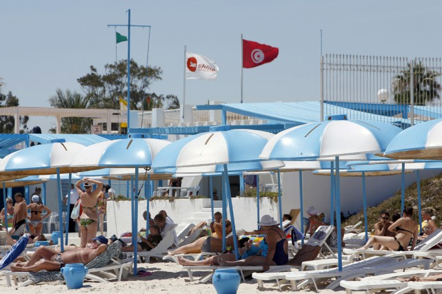 Des touristes prennent un bain de soleil sur... (photo Associated Press)