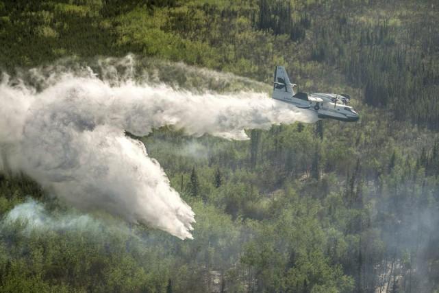 Une avion-citerne survole la forêt dans la région... (Photo fournie par le ministère de l'Environnement de la Saskatchewan)