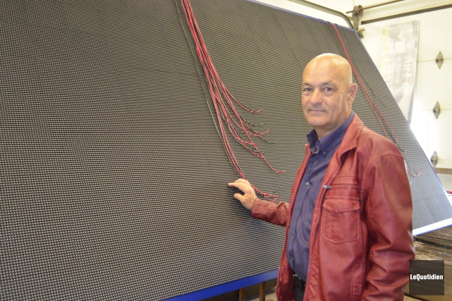 M. Ste-Marie pose devant cette affiche électronoque fabriquée... ((Photo le Quotidien, Laura Lévesque))