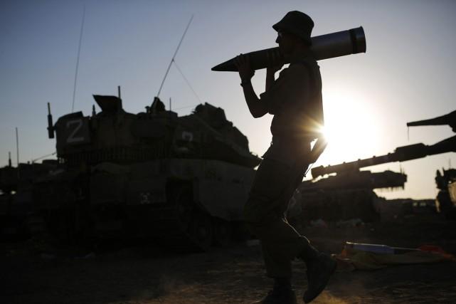 Un soldat israélien transporte un obus alors qu'il... (PHOTO AMIR COHEN, ARCHIVES REUTERS)