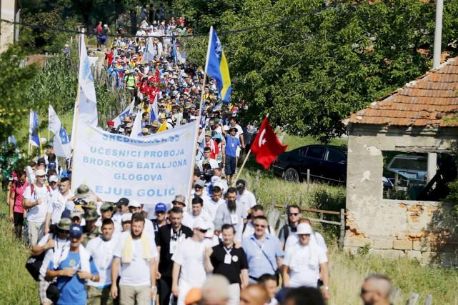 Brandissant des drapeaux blancs frappés de fleurs de... (PHOTO ANTONIO BRONIC, REUTERS)