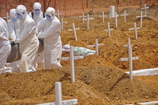Des travailleurs de la santé s'apprêtent à enterrer... (PHOTO ABBAS DULLEH, ARCHIVES AP)