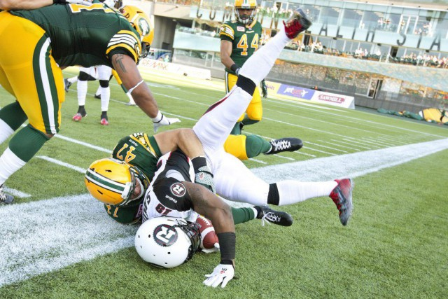Jock Sanders (19) est taclé par JC Sherritt... (Photo JASON FRANSON, PC)