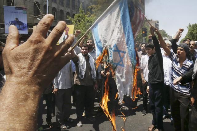 Des manifestants brûlent un drapeau israélien, à Téhéran,... (PHOTO VAHID SALEMI, AP)