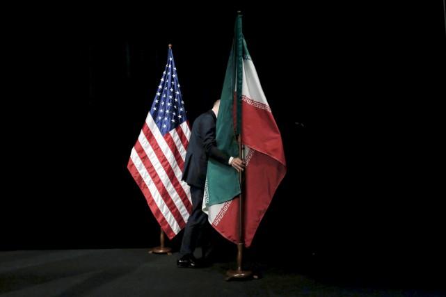 Un membre du personnel déplace le drapeau iranien,... (PHOTO CARLOS BARRIA, REUTERS)