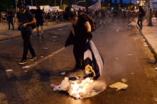 Un manifestant brûle un drapeau grec lors d'une... (PHOTO AFP)