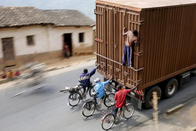 Des cyclistes s'accrochent à un camion, pendant qu'un... (PHOTO MIKE HUTCHINGS, REUTERS)