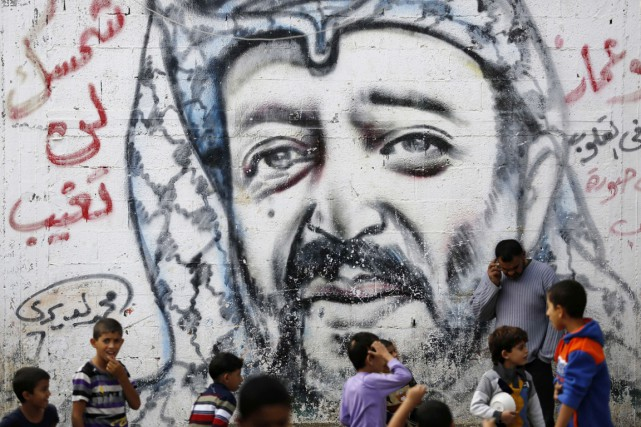 Des garçons palestiniens jouent devant une murale en... (PHOTO MOHAMMED ABED, AFP)