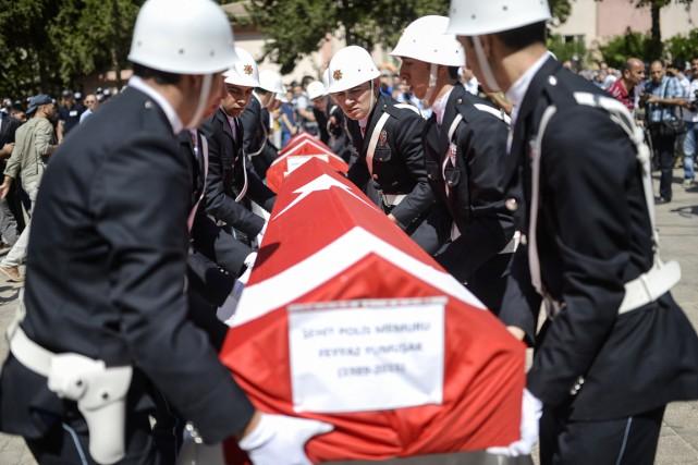 Des policiers turcs portent les cercueils de leurs... (PHOTO BULENT KILIC, AFP)