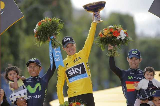 Chris Froome soulève son trophée sur le podium,... (PHOTO LAURENT CIPRIANI, AP)