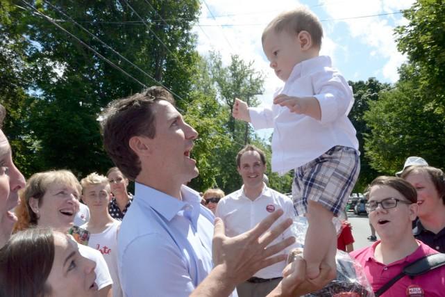 Justin Trudeau tient un bébé en équilibre lors... (La Presse Canadienne)