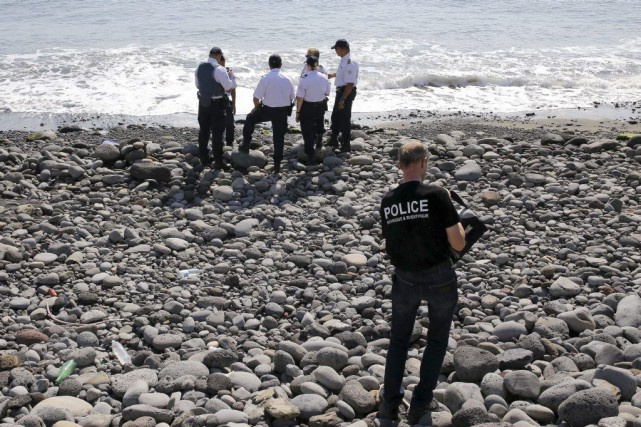 Des policiers inspectent des débris métalliques retrouvés sur... (PHOTO RICHARD BOUHET, AFP)