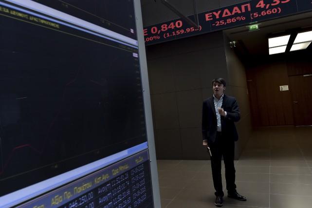 Un homme regarde les données sur les tableaux... (AFP, ARIS MESSINIS)