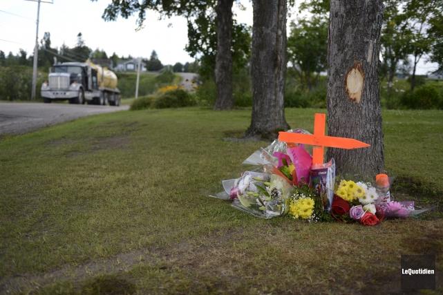 Des fleurs et une croix en bois ont... ((Photo Le Quotidien, Jeannot Lévesque))