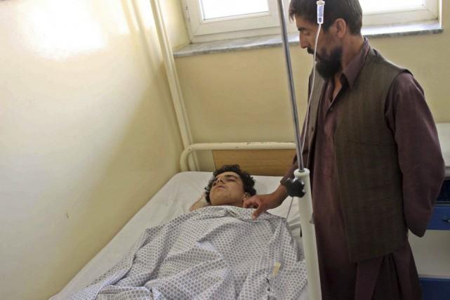 Un homme veille sur un blessé dans l'attentatà... (PHOTO NASIR WAQIF, AFP)
