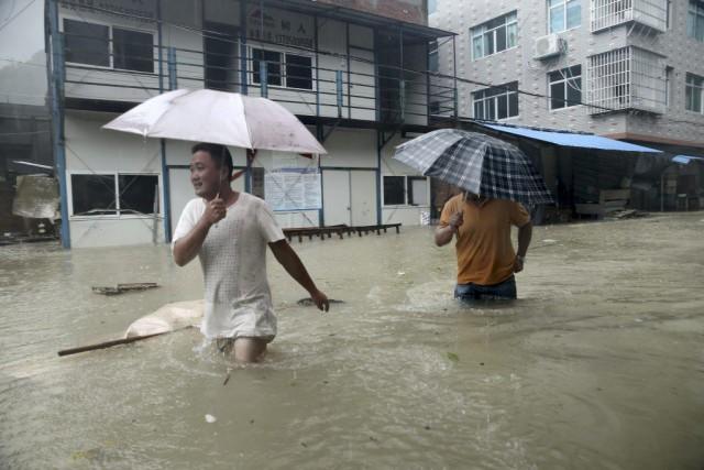 Deux hommes tentent de se frayer un chemin... (PHOTO REUTERS/CHINA STRINGER NETWORK)